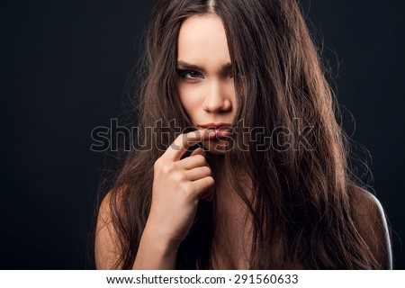 Piercing glance. Confident young shirtless woman holding finger on her lips and looking at camera while standing against black background   - stock photo
