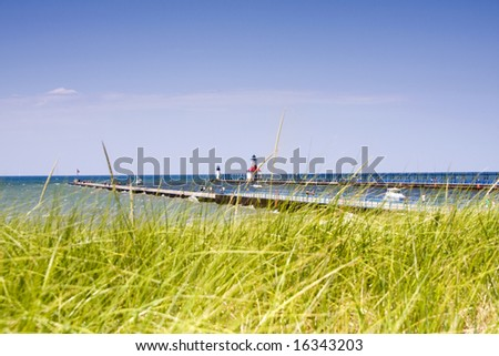 Piers at the harbor entrance to St. Joseph, Michigan, with out of focus dune grass in foreground. - stock photo