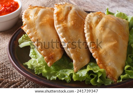 pies empanadas on a plate with lettuce and sauce close up on the table. horizontal  - stock photo