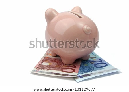 pig bank from back side on euro banknotes - stock photo