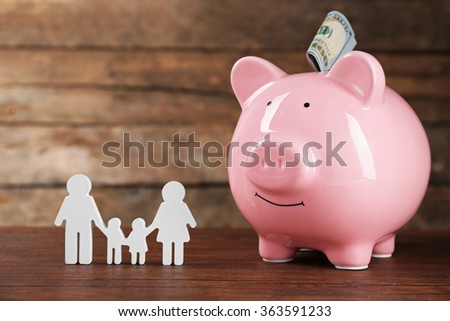 Pig money box and paper decor on wooden wall background - stock photo