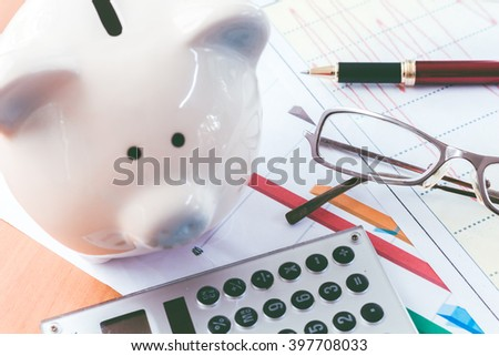 Piggy bank and calculator on business documents background - stock photo