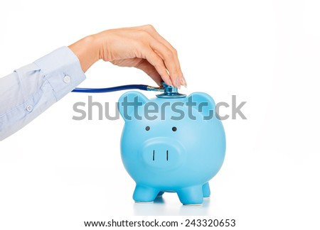 Piggy bank and stethoscope Isolated on white background. Health care cost. Financial state condition self assessment concept. Financial system checkup or saving for medical insurance costs - stock photo