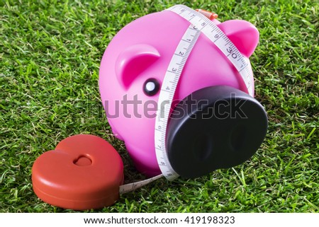 Piggy bank and tape measure on grass - stock photo