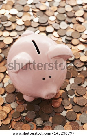 Piggy bank and vast amount of coins - stock photo