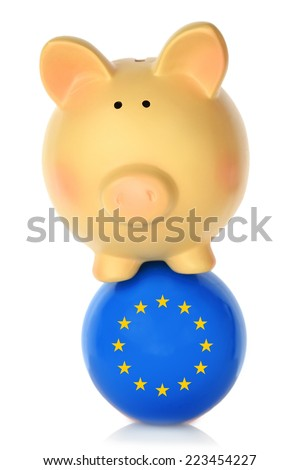 Piggy bank balancing on blue ball with European flag - stock photo