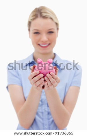 Piggy bank being held by young woman against a white background - stock photo