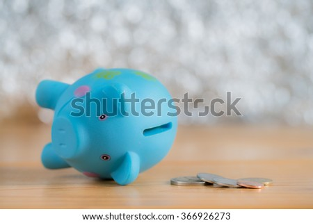 Piggy bank broken down with coins on wooden table, concept for business failure or down - stock photo