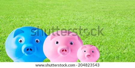 Piggy bank family on grass background  - stock photo
