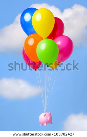 Piggy bank flying in the sky on helium balloons, good image for finance related themes such as Inflation, Savings or Economy. - stock photo