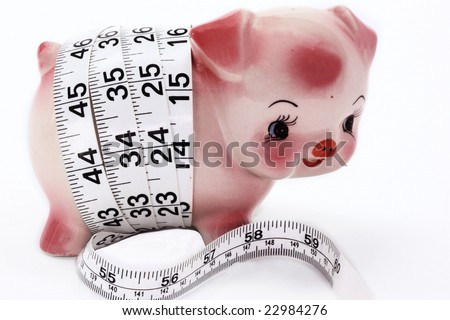 Piggy bank getting measured up with a tape measure. - stock photo