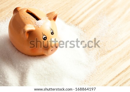 Piggy bank in a heap of white sugar - stock photo