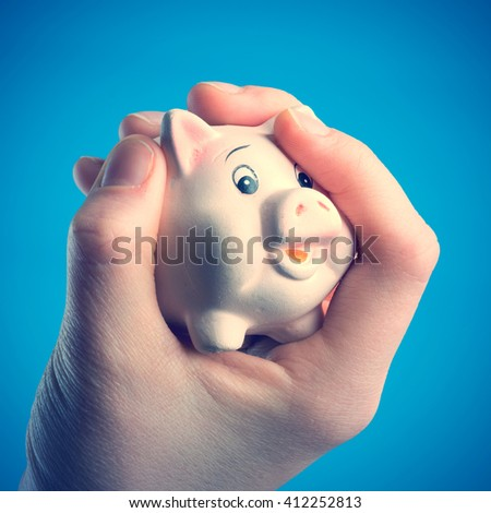 Piggy bank in a human hand on a blue background - stock photo