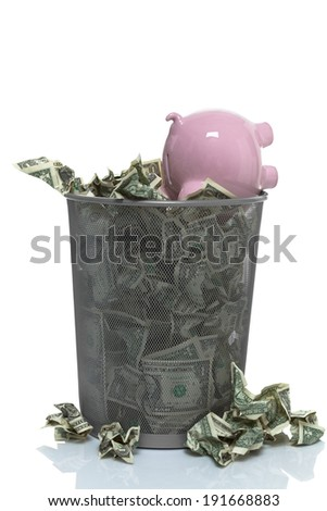 piggy bank in a trash can full of money - stock photo