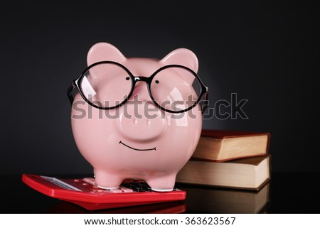 Piggy bank in glasses with calculator and books on dark background - stock photo
