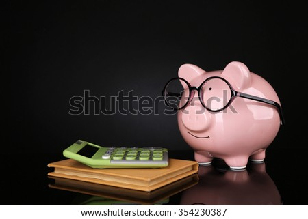 Piggy bank in glasses with calculator and notebook on dark background - stock photo