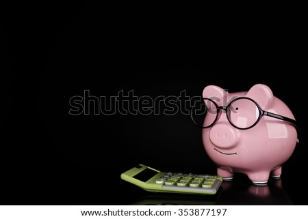Piggy bank in glasses with calculator on dark background - stock photo
