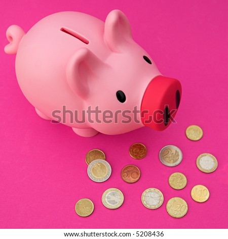 Piggy bank on pink with various Euro coinage around - shallow dof - stock photo
