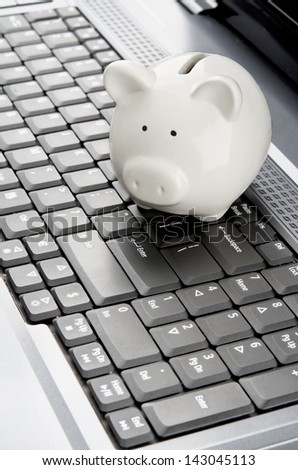 Piggy bank over a laptop keyboard as a symbol of technology and information cost or internet banking - stock photo