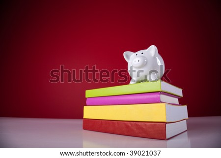 piggy bank over a stack of colorful books with a red background - stock photo