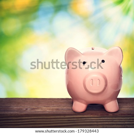 Piggy bank over shiny leaves background - stock photo