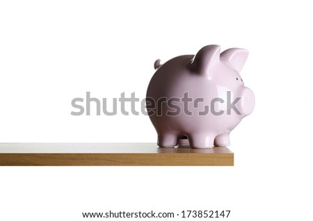 Piggy bank placed close to the edge of a board  - stock photo