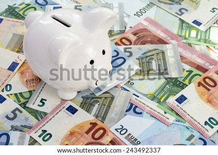 Piggy bank placed on Euro currency. Concept for cut in interest rates, euro crisis and saving - stock photo
