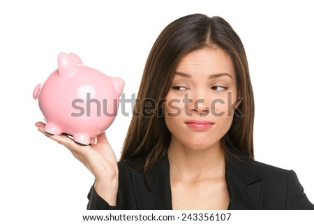 Piggy bank savings with unhappy funny woman looking displeased at pink piggy bank isolated on white background. Business woman or banker wearing suit jacket. Mixed race Asian Caucasian female model. - stock photo
