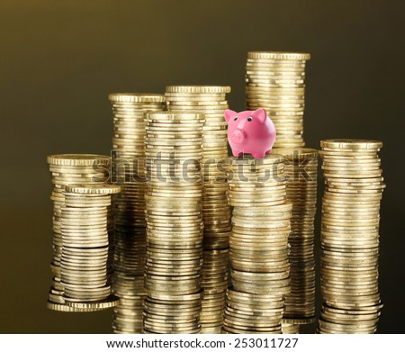 Piggy bank standing on stack of coins on brown background - stock photo