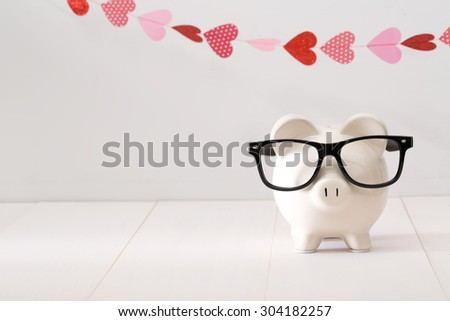 Piggy bank wearing black glasses with a garland of hearts - stock photo