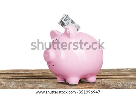 Piggy bank with banknote on wooden table, isolated on white - stock photo