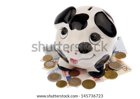 Piggy bank with black and white cow spots, looking upwards and standing on a bed of Euro banknotes and coins, isolated in white background - stock photo