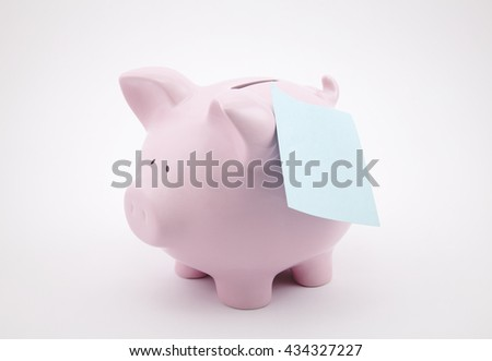 Piggy bank with blank reminder note  - stock photo