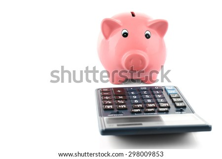 Piggy bank with calculator isolated on white - stock photo
