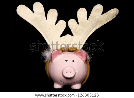 Piggy bank with christmas antlers studio cutout - stock photo