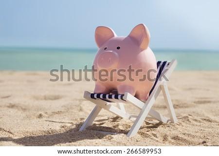 Piggy Bank With Deckchair On Sandy Beach - stock photo