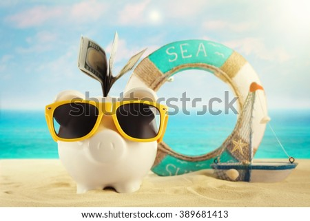 Piggy bank with dollar banknotes, sunglasses on a sand. Holiday money concept - stock photo