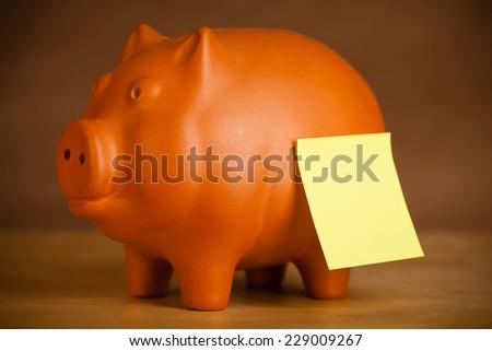 Piggy bank with empty sticky note - stock photo