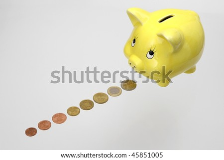 Piggy bank with Euro coins in a line on white background - stock photo