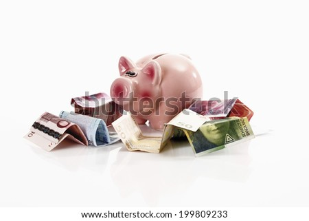 Piggy bank with euro notes and Swiss francs - stock photo