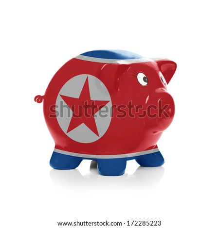Piggy bank with flag coating over it isolated on white - North Korea - stock photo