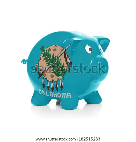 Piggy bank with flag coating over it isolated on white - State of Oklahoma - stock photo