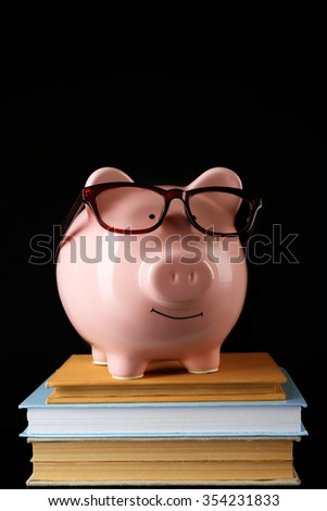 Piggy bank with glasses and books on a black background - stock photo