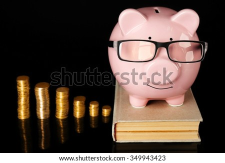 Piggy bank with glasses,book and coins  on a black background - stock photo