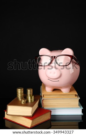 Piggy bank with glasses,coins and books on a black background - stock photo
