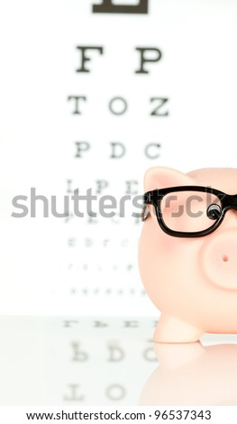piggy bank with glasses on an eye chart background - stock photo