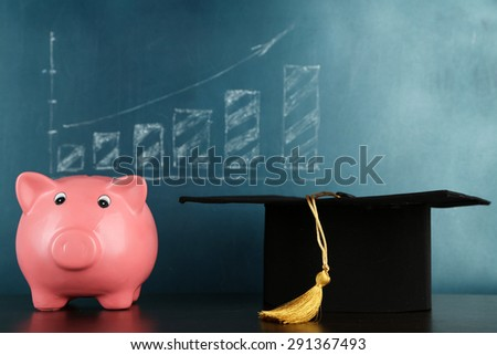 Piggy bank with grad hat on blackboard background - stock photo