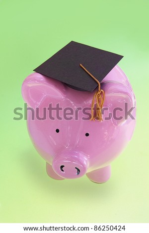 piggy bank with graduation cap on green ( cost of education ) - stock photo