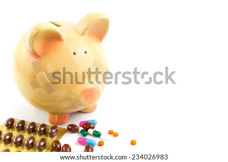 Piggy bank with medical patches and pills isolated on white  - stock photo