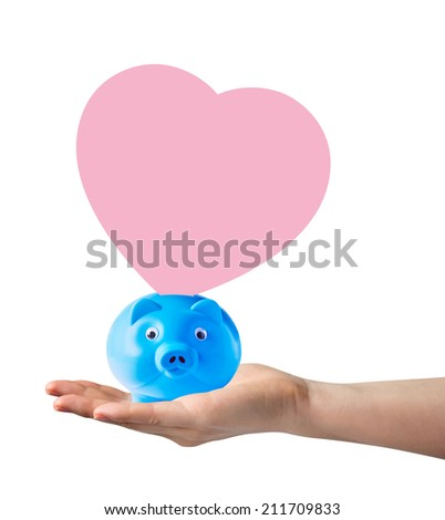 Piggy bank with pink paper shape heart on hand  - stock photo